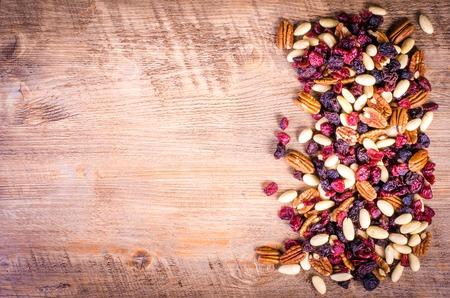 frutas deshidratadas: Frutas secas - pacanas, arándanos, pasas, almendra en el fondo de madera.