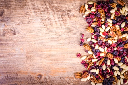 dried fruits: Dried fruits - pecan, cranberry, raisin, almond on wooden background.