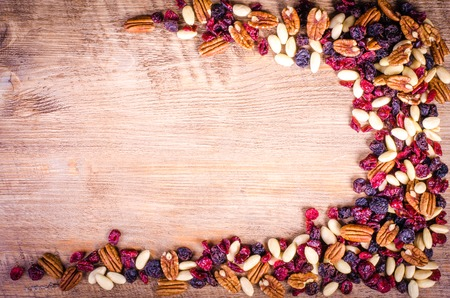 Dried fruits - pecan, cranberry, raisin, almond on wooden background.