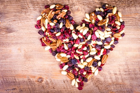 Dried fruits - pecan, cranberry, raisin, almond forming a heart on wooden background