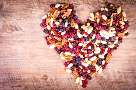 frutos secos: Frutas secas - pacana, arándano, uva pasa, formando un corazón sobre fondo de madera de almendras Foto de archivo