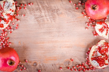 Ripe pomegranate fruit and seeds on wooden background. Eating frame. Stockfoto