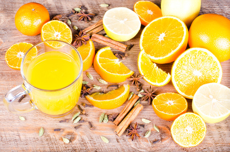 orange peel clove: A closeup of a pile of oranges sliced and fresh orange juice  on wooden background. Eating frame. Free space for text