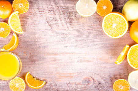 A closeup of a pile of oranges sliced and fresh orange juice  on wooden background. Eating frame. Free space for text