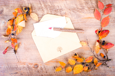 pensil: Colorful autumn leaves, envelope and pensil lying on diary, notebook, wooden background. Fall and thanksgiving. Autumn composition. Free space for text. Stock Photo