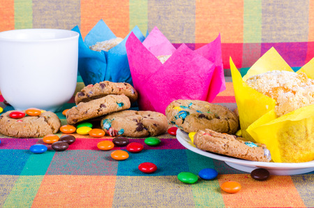 Fresh homemade muffins and cookies with color chocolate coated candies, cup of tea on a colorful checkered kitchen towel. Free space for your text