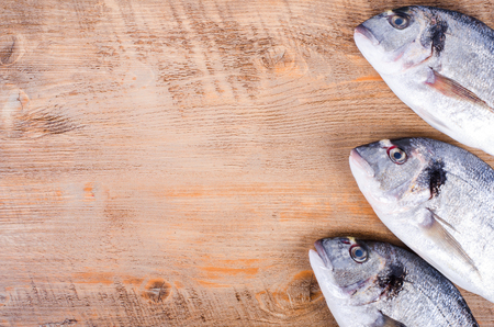 gilthead: Fresh raw gilthead fishes on wooden background. Healthy food concept. Food frame.