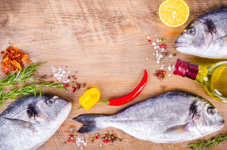 gilthead: Fresh raw gilthead fishes with lemon, herbs, olive oil, salt on wooden background. Healthy food concept. Food frame