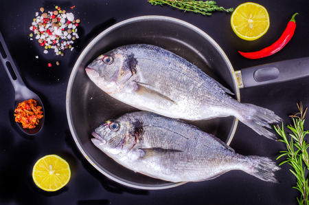 sparus: Fresh raw gilthead fishes with lemon, herbs, salt on black background. Healthy food concept. Food frame