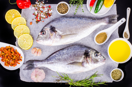 gilthead: Fresh raw gilthead fishes with lemon, herbs, salt on black background. Healthy food concept. Food frame
