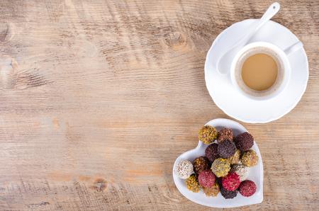 cafe bombon: Dulces de chocolate hechas a mano en la formación de placa de corazón y la taza de café, fondo de madera. Espacio libre para el texto. Foto de archivo