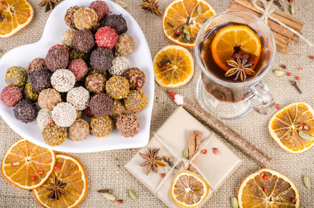 handmade: Handmade chocolate candies collection, dried oranges, spices, mulled wine, wooden pencil on wooden background. Christmas, New Year and winter. Stock Photo