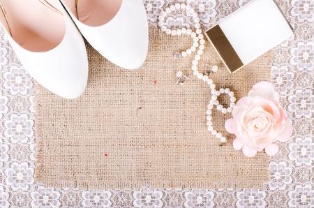 Mooie set van vrouwen bruiloft accessoires. Ochtend bruid. Witte schoenen, parfum, parel ketting en oorbellen op wit kant doek en een zak, canvas.