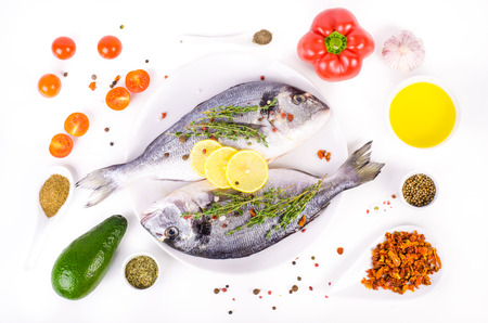 gilthead: Fresh raw gilthead fishes with lemon, herbs, olive oil, avocado, paprika, ?herry tomatoes, garlic, salt on white background. Healthy food concept. Food frame Stock Photo