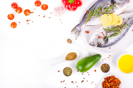 Fresh raw gilthead fishes with lemon, herbs, olive oil, avocado, paprika, ?herry tomatoes, garlic, salt on white background. Healthy food concept. Food frame. Free space for your text Standard-Bild
