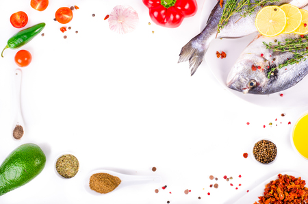 gilthead: Fresh raw gilthead fishes with lemon, herbs, olive oil, avocado, paprika, ?herry tomatoes, garlic, salt on white background. Healthy food concept. Food frame. Free space for your text Stock Photo