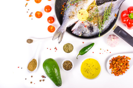 gilthead: Fresh raw gilthead fishes with lemon, herbs, salt on white background. Healthy food concept. Food frame
