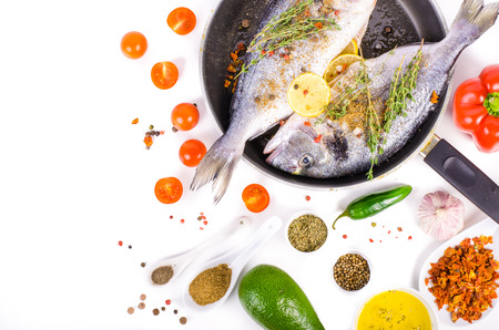 gilthead: Fresh raw gilthead fishes with lemon, herbs, salt on white background. Healthy food concept. Food frame. Free space for your text.