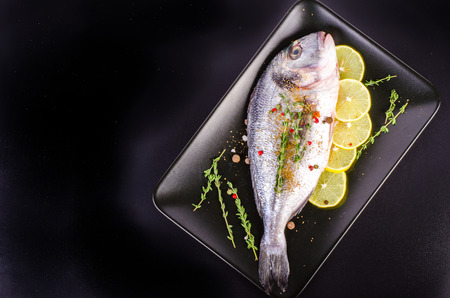 sparus: Fresh raw gilthead fishes with lemon, herbs, salt on plate, black background. Healthy food concept. Food frame