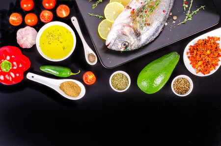 gilthead: Fresh raw gilthead fishes with lemon, herbs, salt on black background. Healthy food concept. Food frame. Free space for your text.