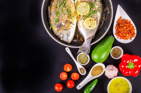 gilthead: Roasted gilthead fishes with lemon, herbs, salt on black background. Healthy food concept. Food frame. Free space for your text.