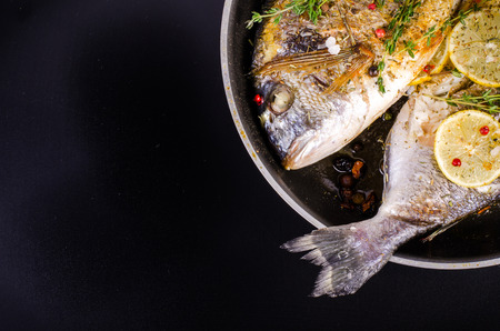 sparus: Roasted gilthead fishes with lemon, herbs, salt on black background. Healthy food concept. Food frame. Free space for your text.