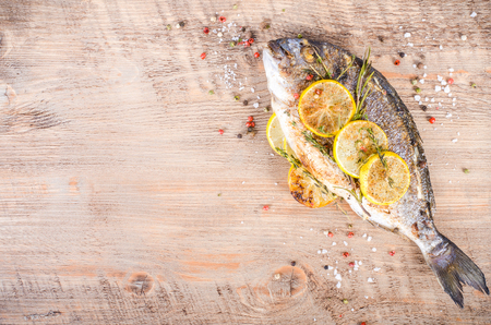 gilthead: Roasted gilthead fishes with lemon, herbs, salt on wooden background. Healthy food concept. Food frame. Free space for your text.