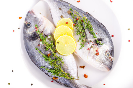 gilthead: Fresh raw gilthead fishes with lemon, herbs, salt on plate, white background. Healthy food concept. Food frame