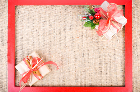 fibber: Two Christmas gifts with red tapes over sackcloth texture background, free space for your text.