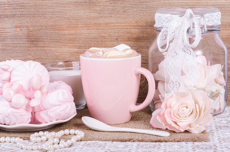 sweet background: Cute set of pink princess accessories and sweets. Bottle with mastic flowers, big peach rose, zefir, cup of cacao with marshmellow, little spoon and pearl jewerly.
