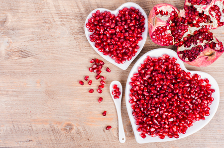 Two white heart shaped plates full of fresh ripe juicy pomegranate seeds, little spoon, whole fruit and ripe one on wooden background.