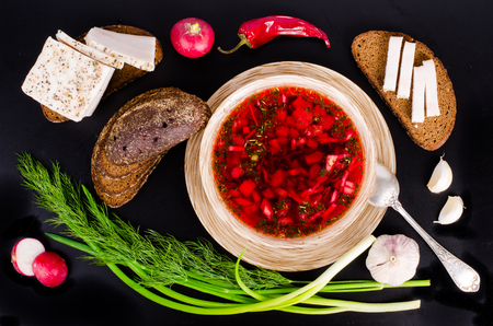 Beetroot soup in bowl with salted fresh lard, garlic, green onion, red pepper and rye bread on black background.