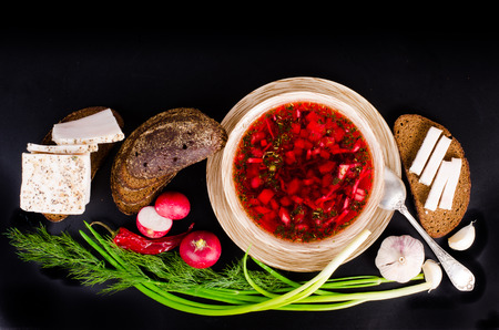 salo: Ukrainian beetroot soup - borscht in bowl with salted fresh lard - salo, garlic, green onion, red pepper and rye bread on black background.