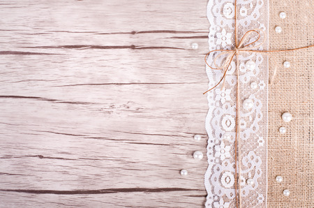 Lace, pearls, bowknot, canvas, sackcloth on wooden background. Rustic design. Free space for your text Stockfoto