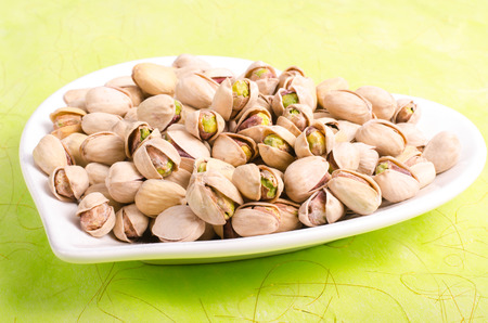 Salt pistachios on the white plate on green background. Stock Photo