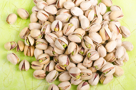 sports shell: Pistachios on bright green background. Stock Photo