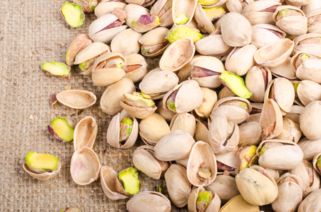 sports shell: Pistachios on sackcloth, canvas background.
