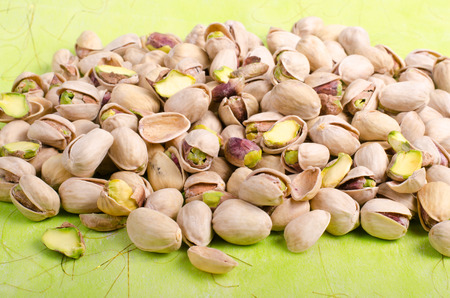 ingridients: Pistachios on bright green background. Stock Photo
