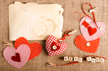 darning needle: Sewing set: fabrics, threads, pins, buttons, tape, handmade hearts, words with love on cubes, burlap, sackcloth background. Retro design effects. Stock Photo