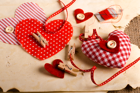 handmade: Sewing set: fabrics, threads, pins, buttons, tape and handmade hearts on vintage paper background. Retro design effects.
