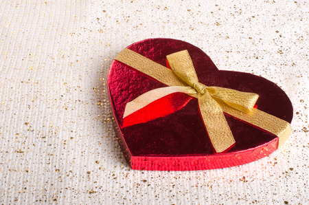 pretty s shiny: Red box in heart shape with gold bow. Valentines day