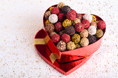 fancy sweet box: Handmade chocolate candies in red heart shape box with gold bowknot. Free space for your text