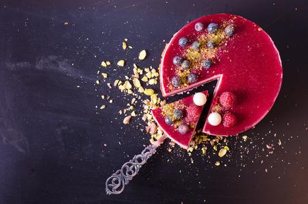 Heerlijke frambozen taart met verse aardbeien, frambozen, bosbessen, krenten en pistachenoten op houten achtergrond. Vrije ruimte voor uw tekst. Stockfoto