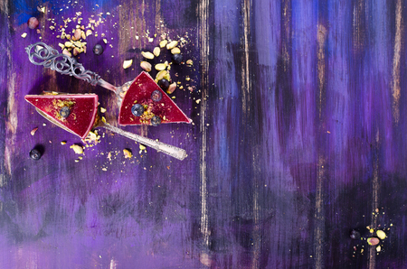 blue violet bright: Pieces of delicious raspberry cake with fresh raspberries, blueberry, currants and pistachios on shovel, bright violet, blue background. Free space for your text. Stock Photo