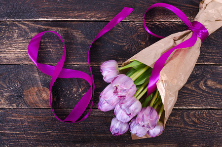 March 8 background. Violet tulips, tape formed number eight on wooden background.