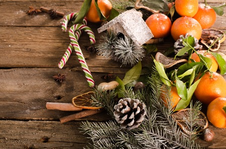 nesting: Christmas background - vintage wood, candy cane, house, cinnamon, star anise, sweet mandarins. Top view, blank space
