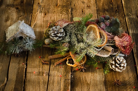 nesting: Christmas background - vintage wood, little house, cinnamon, star anise, dry oranges, cones, snow. New Year. Top view, blank space