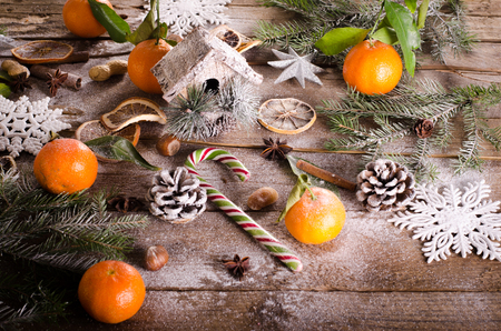 Magic Christmas background - vintage wood, candy cane, house, cinnamon, star anise, sweet mandarins with green leaves, cones, snowflakes. New Year. Top view, blank space Stock Photo