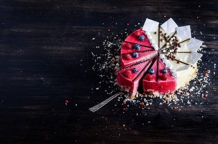Delicious raspberry cake with fresh raspberries, blueberry, almond slices, rose pepper and chocolate cheesecake on black background.