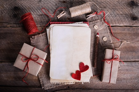 Sewing set: fabrics, threads, pins, buttons, tape and handmade hearts on burlap, sackcloth background. Retro design effects.